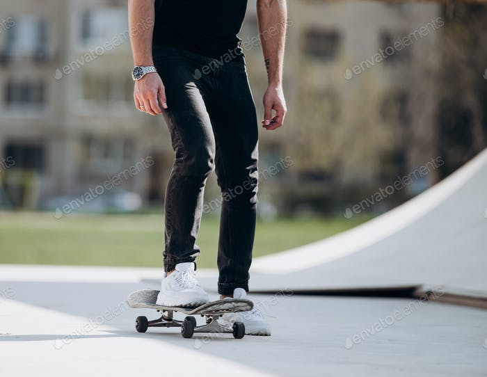 The man rides skateboard on a platform outside next to the house at the sunny warm day