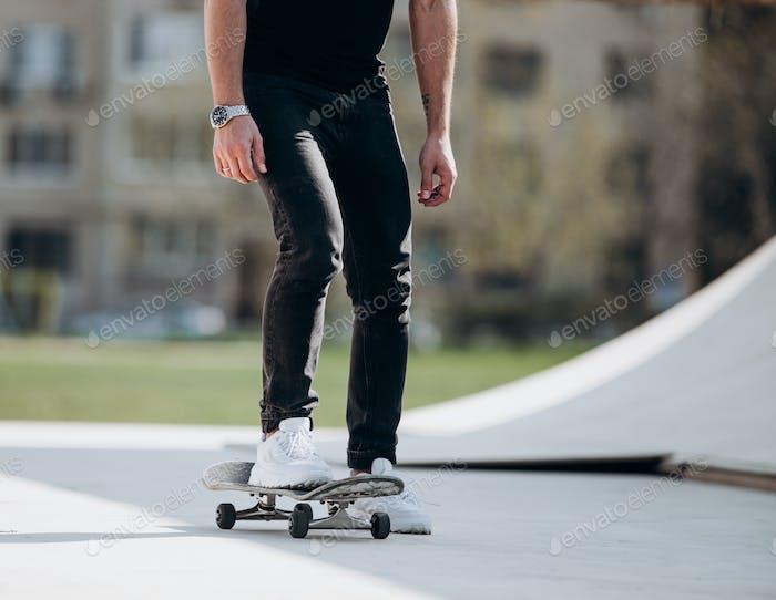 Der Mann fährt am sonnigen warmen Tag Skateboard auf einer Plattform neben dem Haus