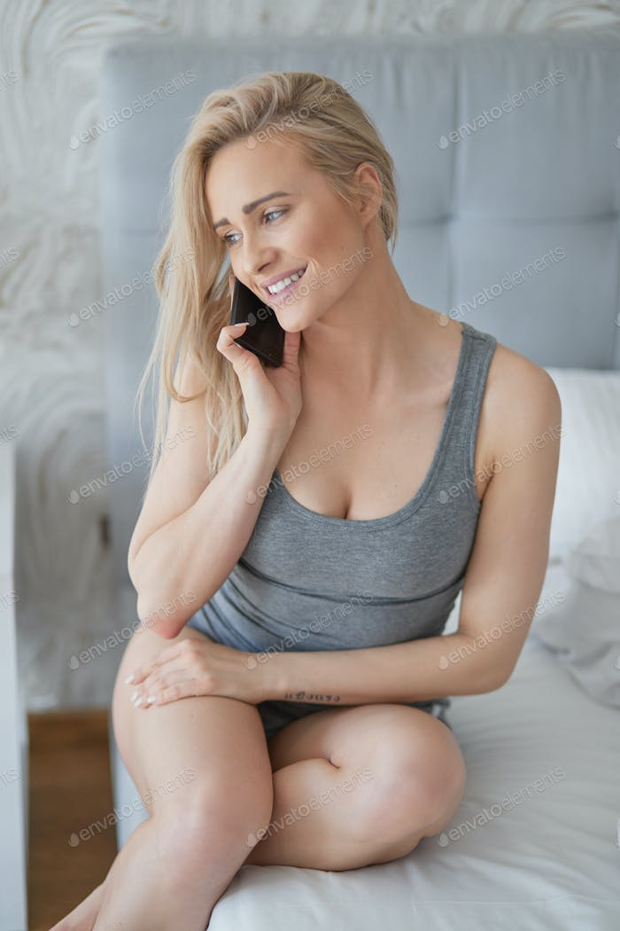Adorable middle aged blonde woman sitting on bed and talking on mobile phone