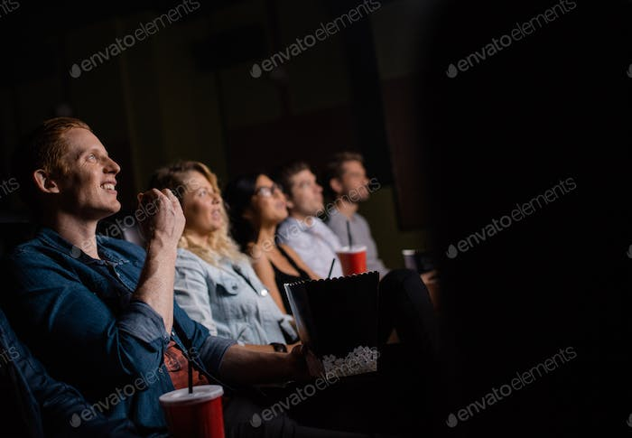 Young man watching movie with friends in cinema