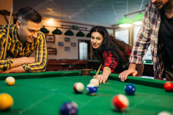 Billiard players with cues at the table with balls