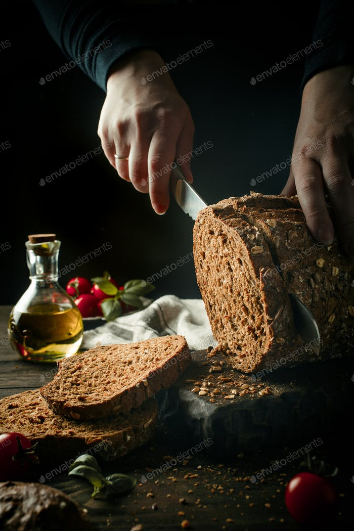Female hands slicing homemade multigrain bread
