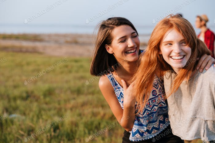 Two cheerful women laughing and having fun outdoors