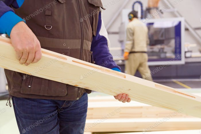 Carpenter with a planed board in his hands, a close-up of a worker at the enterprise.