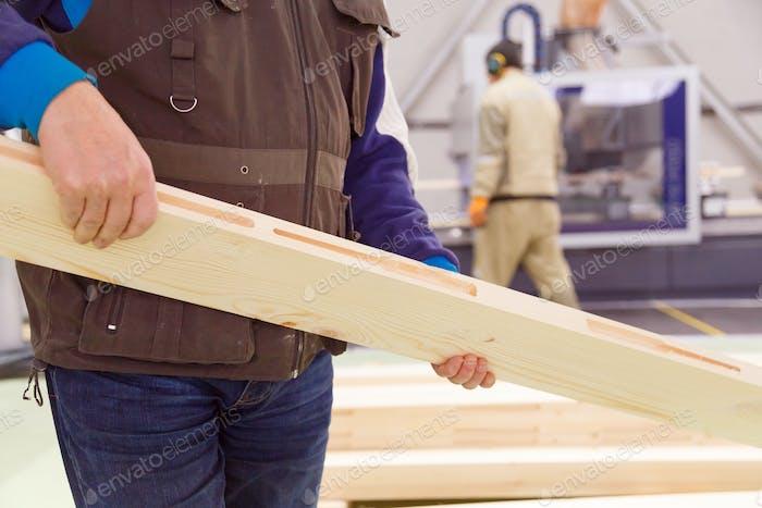 Zimmermann mit einem gehobelten Brett in den Händen, eine Nahaufnahme eines Arbeiters im Unternehmen.
