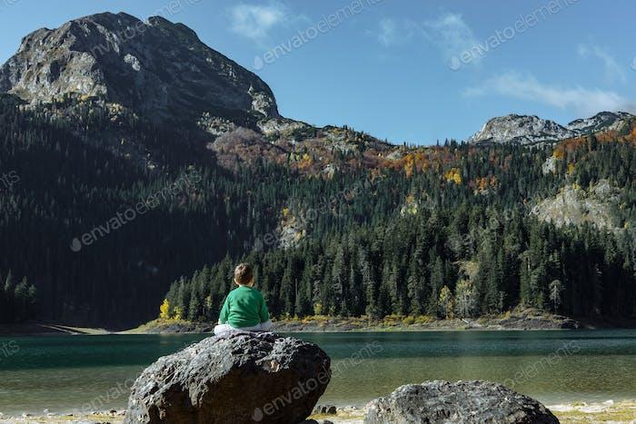 Boy sitting on a big rock and enjoys views of Autumn Black Lake