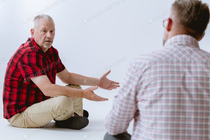 Sad grey senior man sitting on the floor during group psychotherapy for men