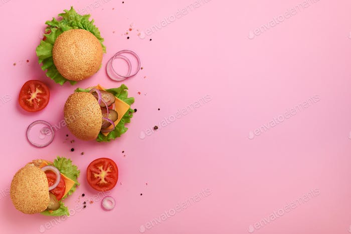 Delicious burgers, cheese, lettuce, onion, tomatoes on pink background. Close up banner. Unhealthy