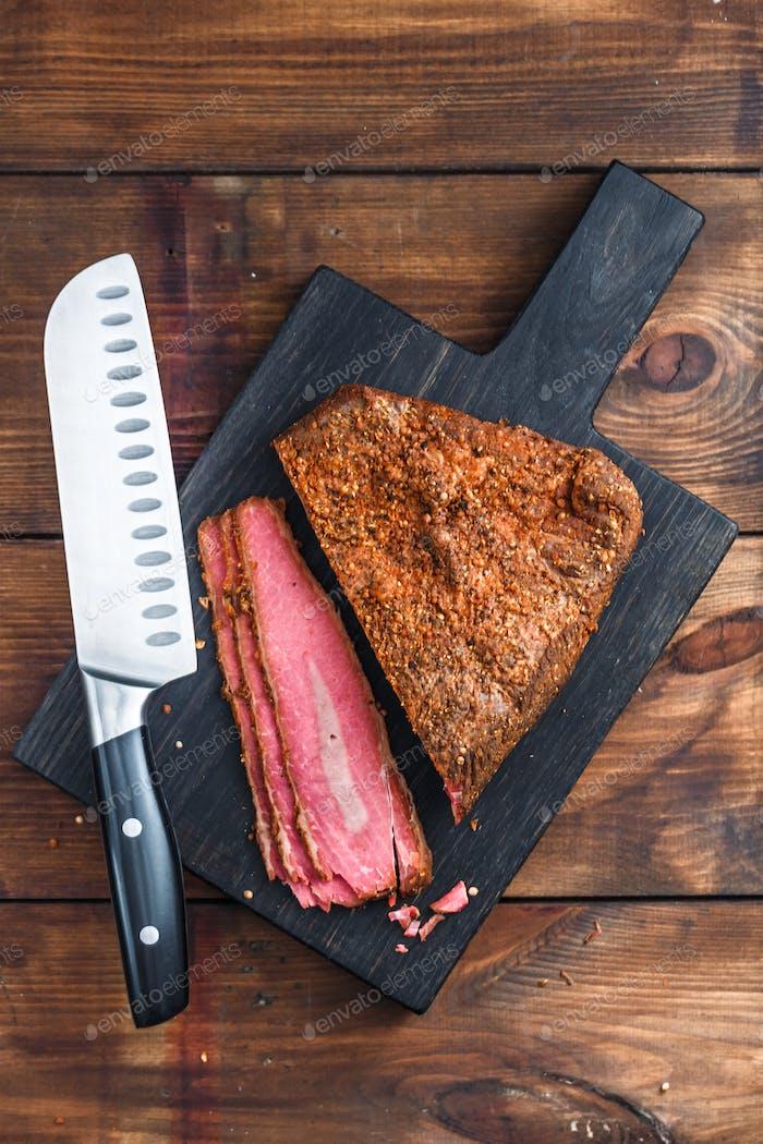 Deli Beef pastrami sliced on wooden board