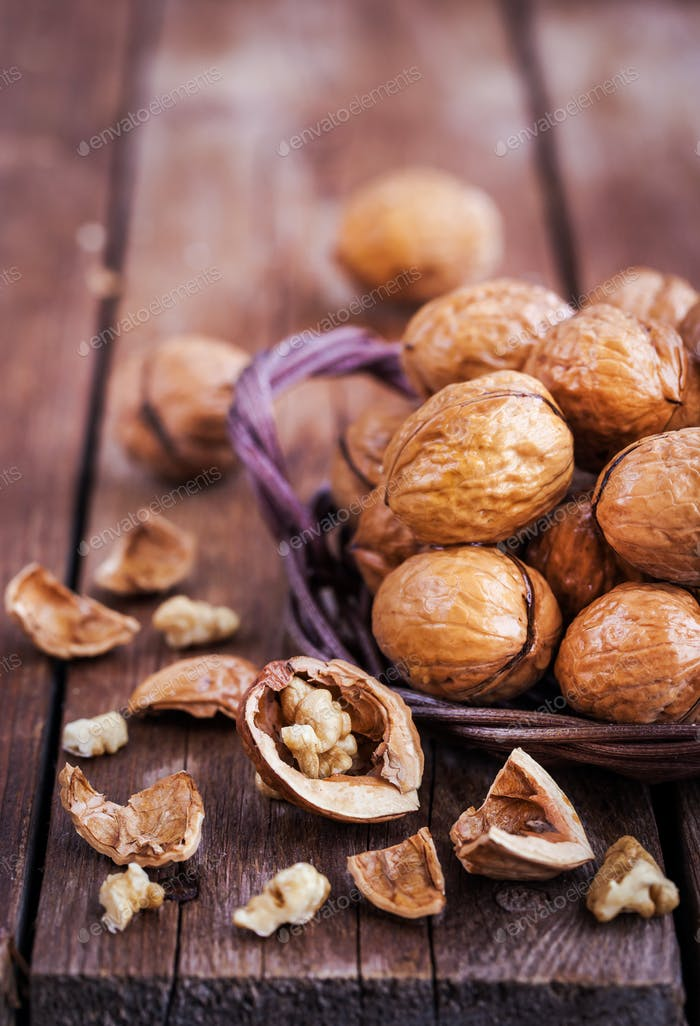 Whole walnuts in basket on rustic old wooden table