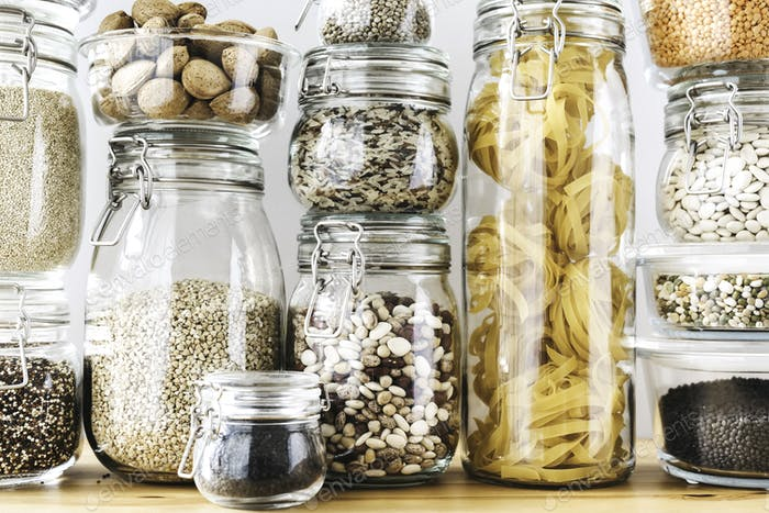 Assortment of uncooked grains, cereals and pasta in glass jars on wooden table. Healthy cooking