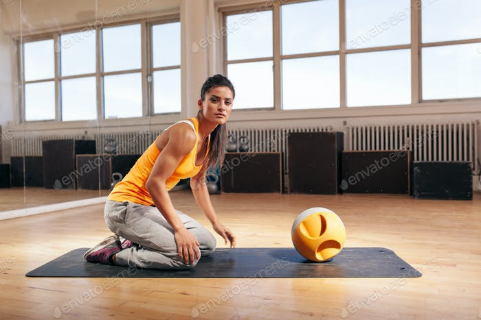 Muscular young woman exercising at gym with kettlebell