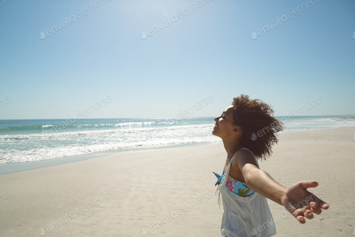 Side view of African american woman standing with arms outstretched on the beach