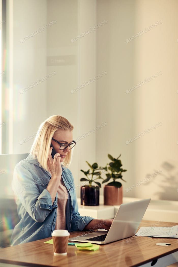 Focused young businesswoman talking on a cellphone in her office