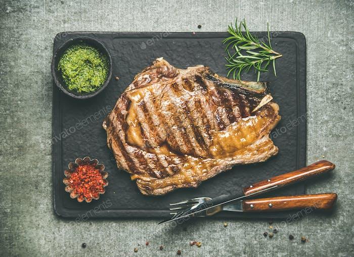 Grilled hot rib-eye beef steak on bone with chimichurri sauce