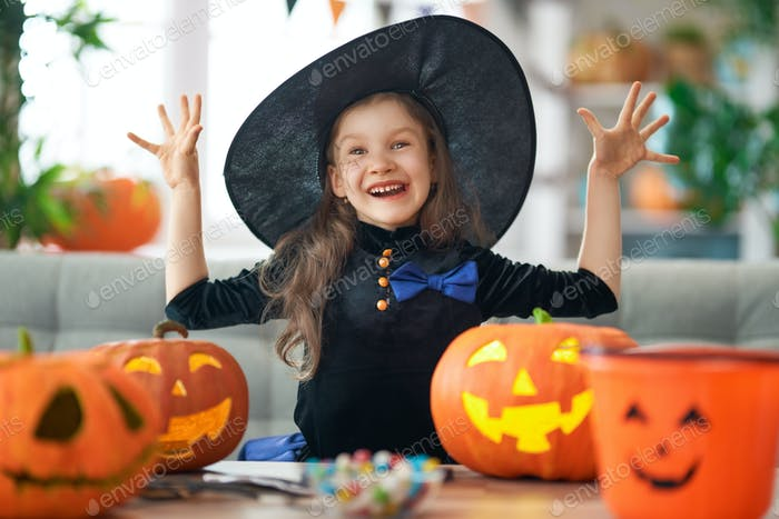 little laughing girl in witch costume