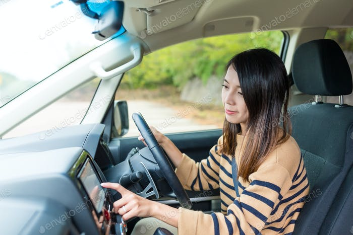 Woman driving a car and touch on GPS
