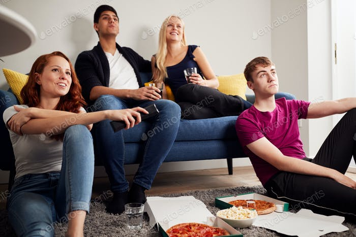 Group Of College Students In Shared House Watching TV And Eating Pizza