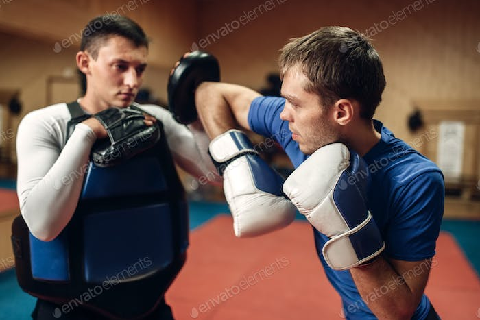 Male kickboxer in gloves practicing elbow kick