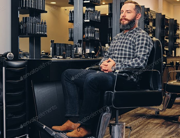 A man dressed in a fleece shirt and jeans sits on a chair in hai