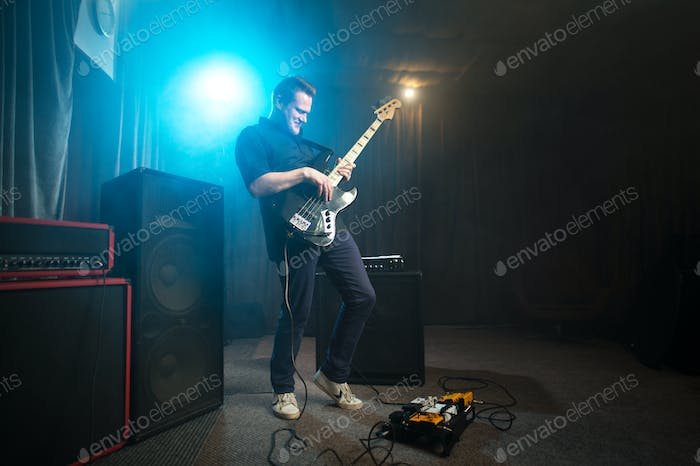 Musician playing an electric bass guitar on stage