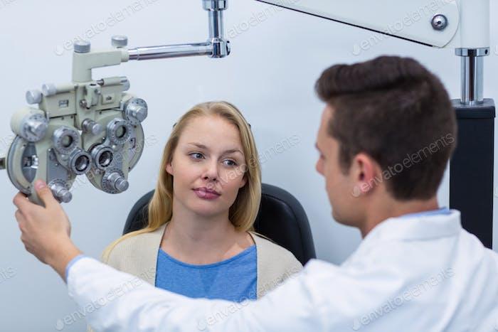 Optometrist interagiert mit weiblichen Patienten