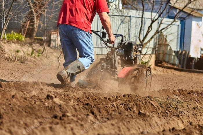 Gärtner bewirtschaften Boden mit Pinnentraktor oder Rototiller, Kutivator