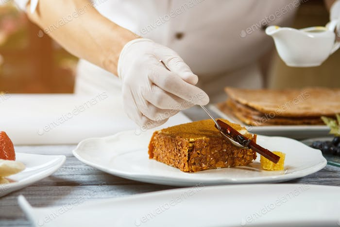 Hand with spoon beside cake