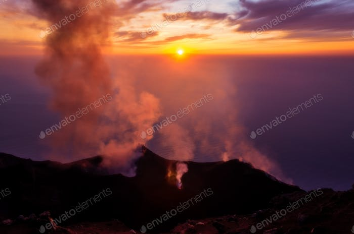 Smoking erupting volcano on Stromboli island at colorful sunset, Sicily