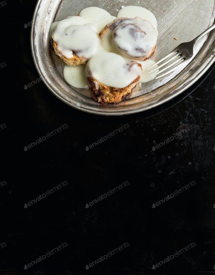 Cinnamon rolls with cream icing and sugar powder on a metal dish