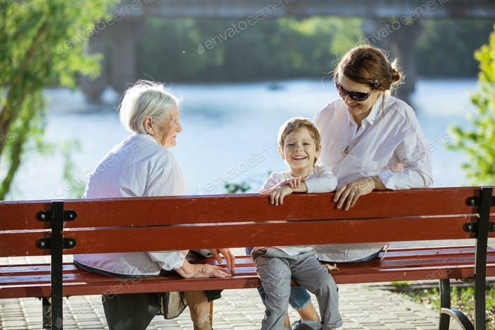 Senior woman, her adult granddaughter and great grandson in park