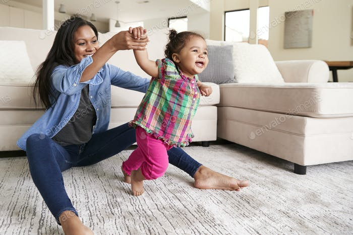 Mother At Home Encouraging Baby Daughter To Take First Steps