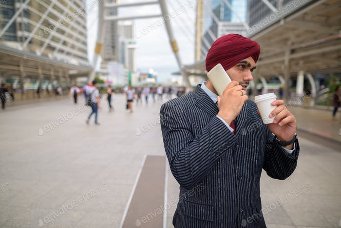 Indian businessman outdoors in city talking on phone and having coffee
