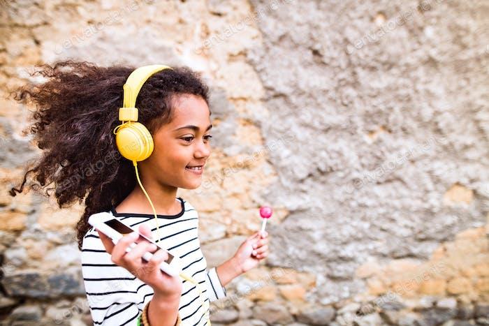 Beautiful african american girl with headphones, listening music