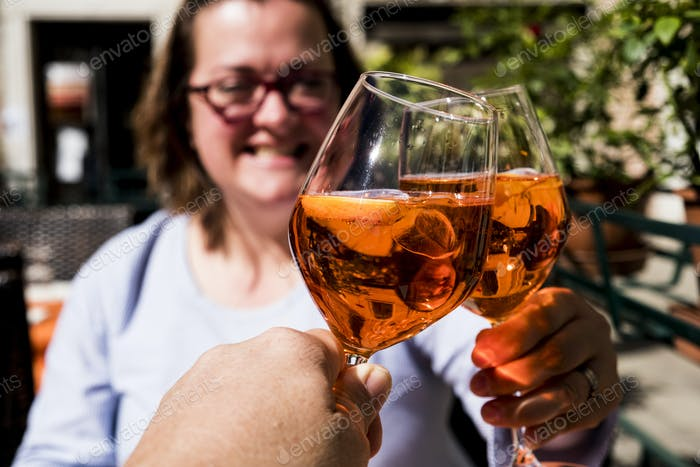 Woman and another person sitting at a table toasting with wine glasses of Aperol Spritz.