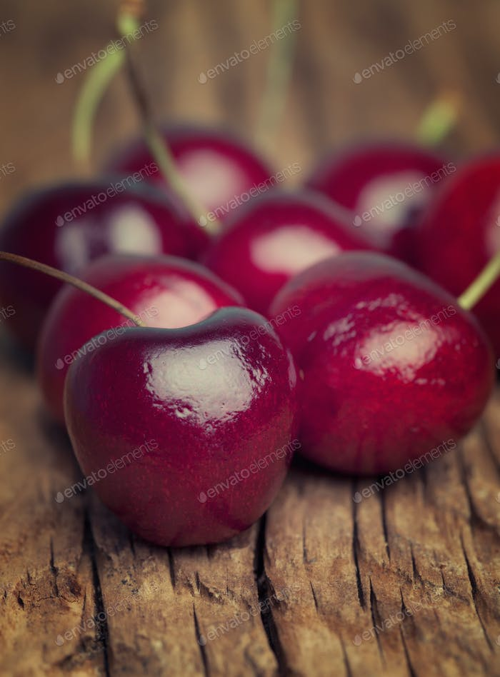 Close up of fresh cherries berries on an old wood