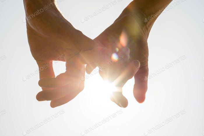 Couple holding hands toward the sun