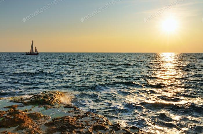 Beautiful sunset over wavy Black sea rocky coastline and yacht at horizon