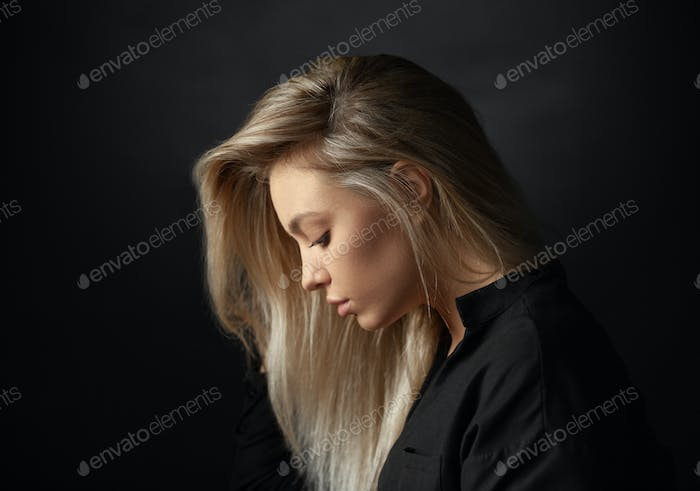 Dramatic studio portrait of beautiful young woman on dark background