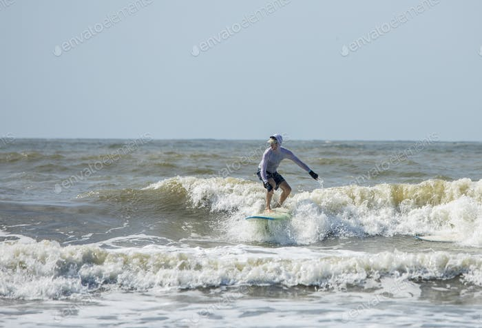 Middle aged man surfs on a longboard in the Atlantic.