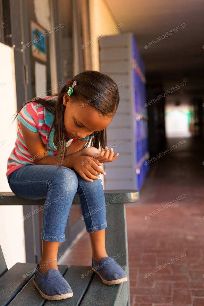 Front view of a sad mixed-race schoolgirl sitting alone on the bench in the corridor at school
