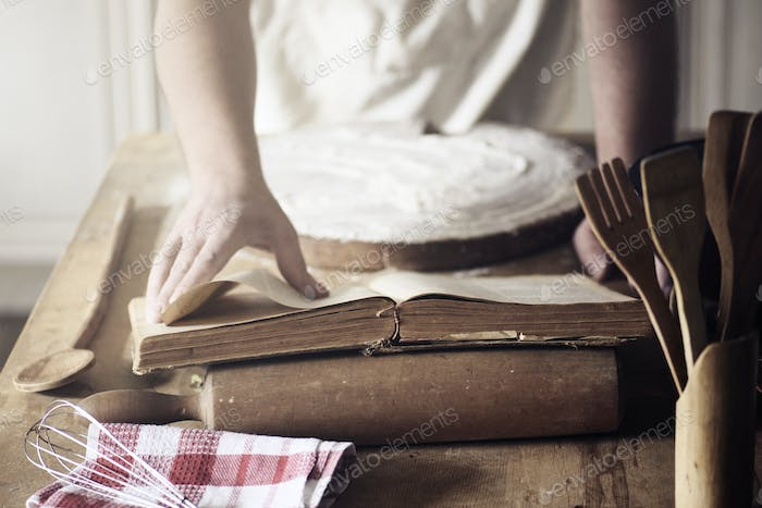 Man preparing traditional recipe from vintage cookbook.