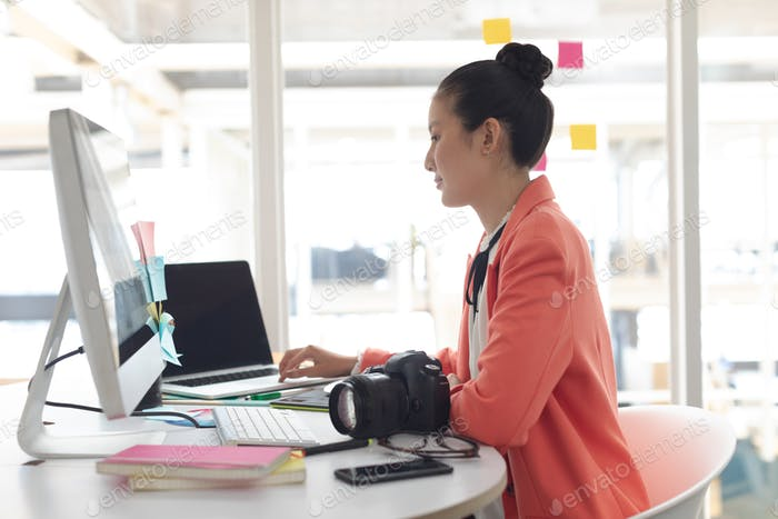 Side view of Asian female graphic designer working on laptop at desk in a modern office