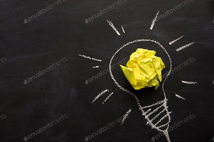 Electric bulb drawn on chalkboard with yellow paper for glowing light