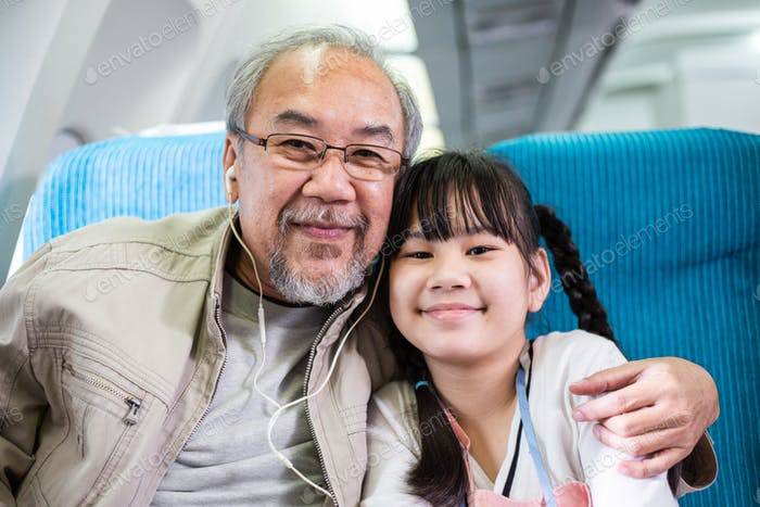 Portrait of Asian grandfather and granddaughter on airplane