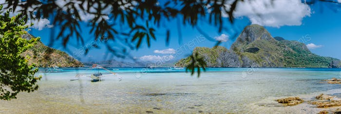 Panorama view of El Nido bay and Cadlao island framed with green branch, blue lagoon, unique nature