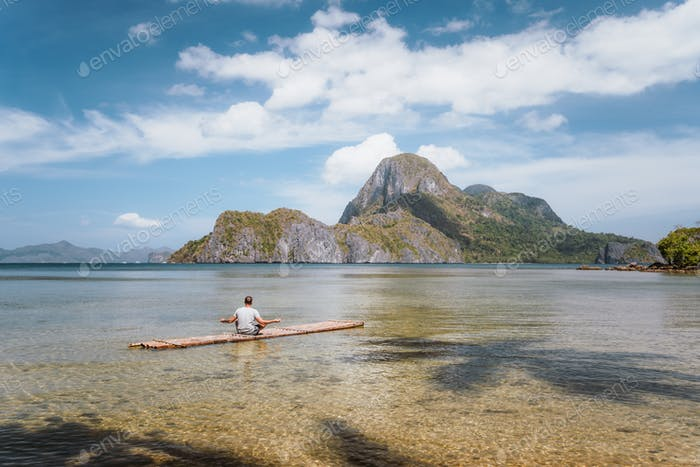 Man meditating on bamboo float in shallow lagoon water and Islands of Cadlao bay in a distance