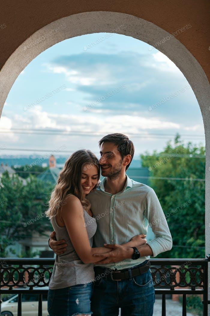 Portrait couple hugging on balcony