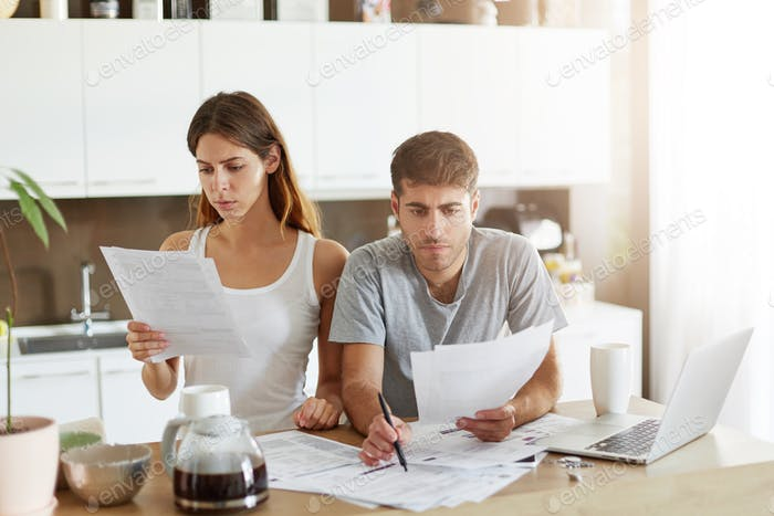 Serious male and female sitting close to each other, looking through finances, planning family budge