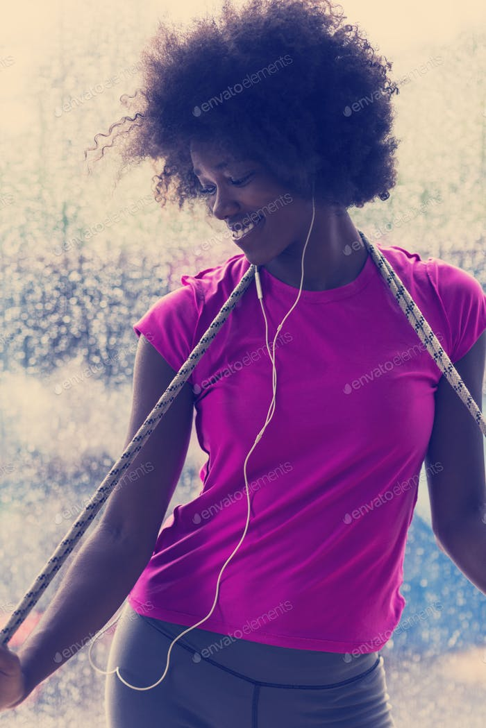 portrait of young afro american woman in gym while listening mus